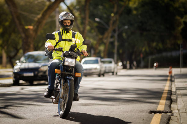 Delivery biker riding down the street - motoboy stock photo