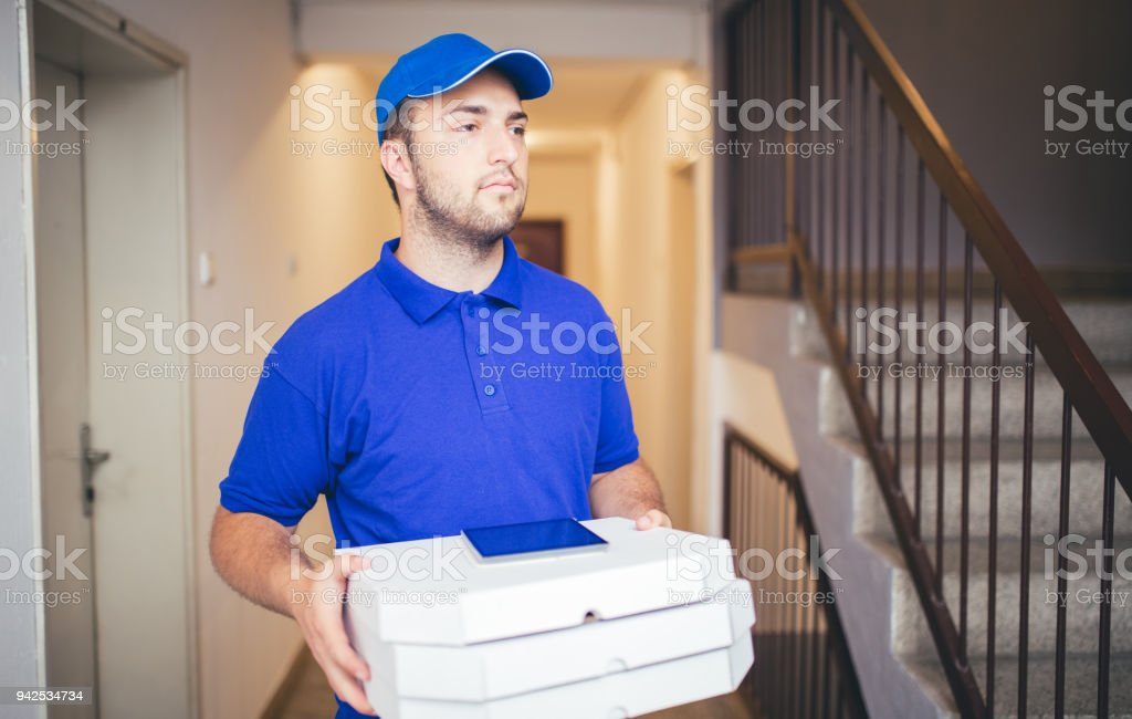 Delivery boy bringing pizza stock photo
