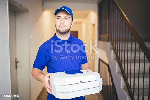 Delivery boy in a blue uniform holding a stack of pizza boxes making a home delivery as seen through a spyhole