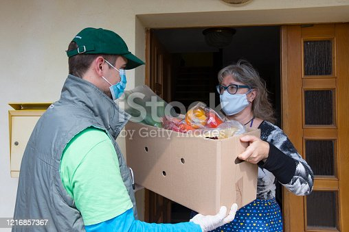 Delivery Boy Delivering Groceries To Front Door of a Mature Woman During Coronavirus Quarantine.