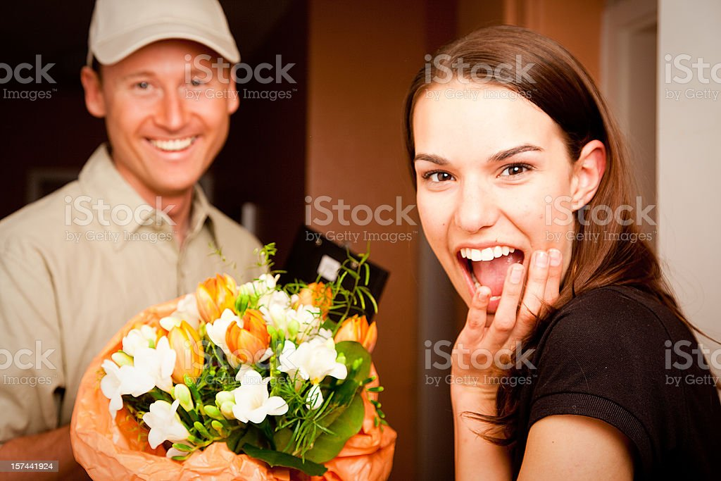 delivery boy handing over flowers royalty-free stock photo