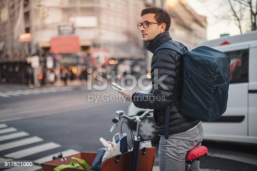Delivery boy on a cargo bike, looking for the right direction