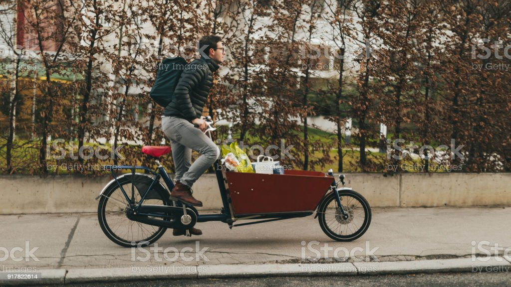 Delivery boy on a cargo bike stock photo