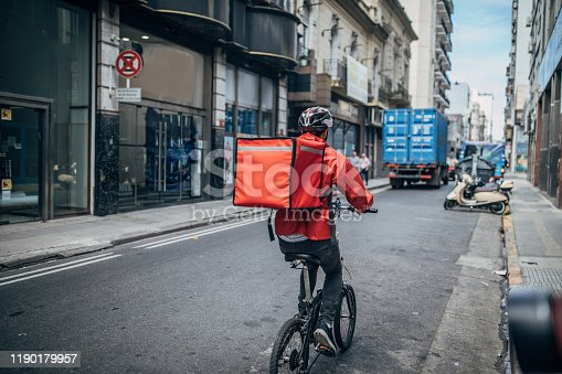 One man, delivery boy on bicycle, delivering pizza in city.