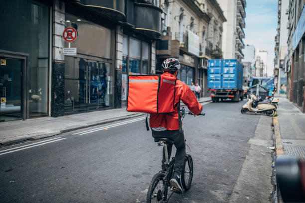 delivery boy on bicycle in city - food delivery imagens e fotografias de stock