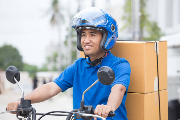 bote auf dem motorrad mit dem stamm paket feld fahren zu schnell in eile. kurier liefern online bestellen. express-lieferung innerhalb der angegebenen zeit von roller-konzept - kinder die schnell arbeiten stock-fotos und bilder