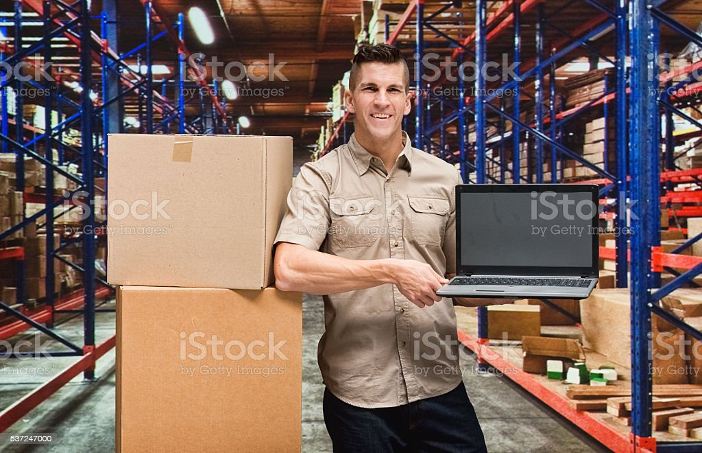 Delivery boy showing laptop stock photo