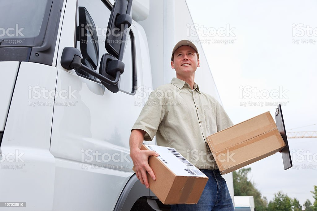 delivery boy standing next to a truck stock photo