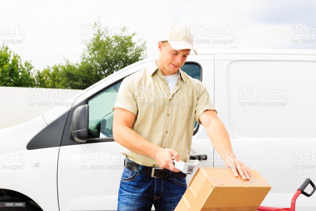 delivery boy standing next to his van stock photo