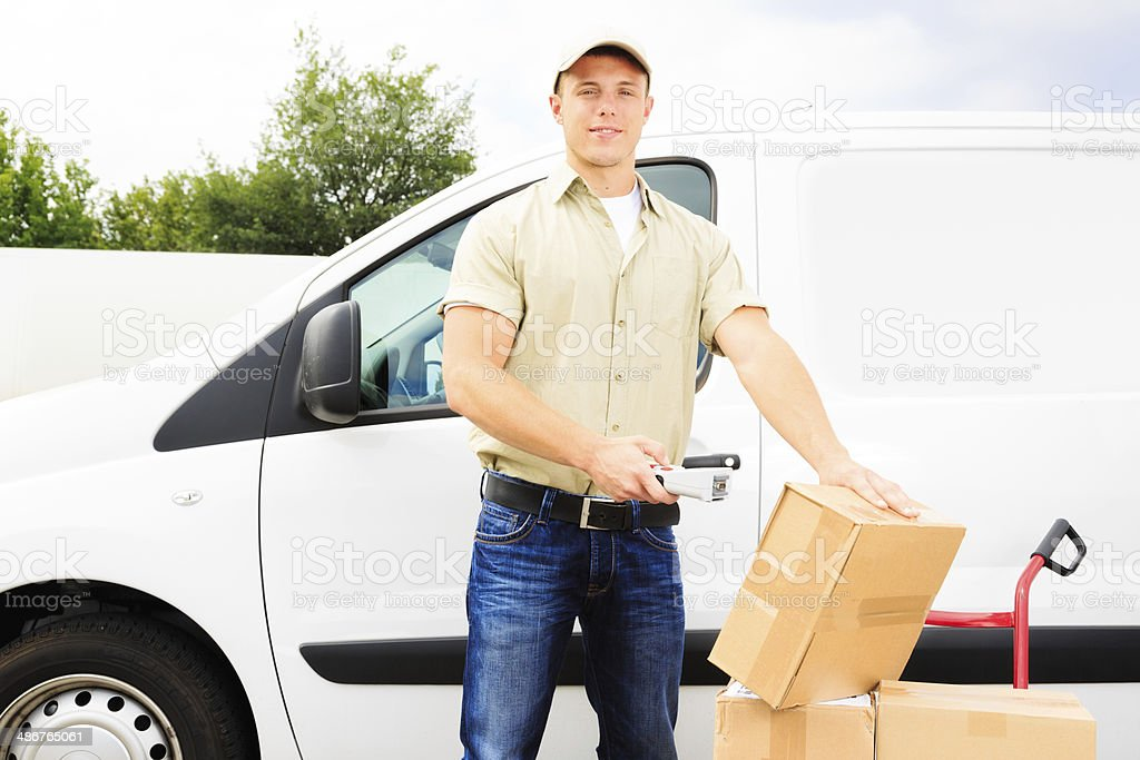 delivery boy standing next to his van stock photo