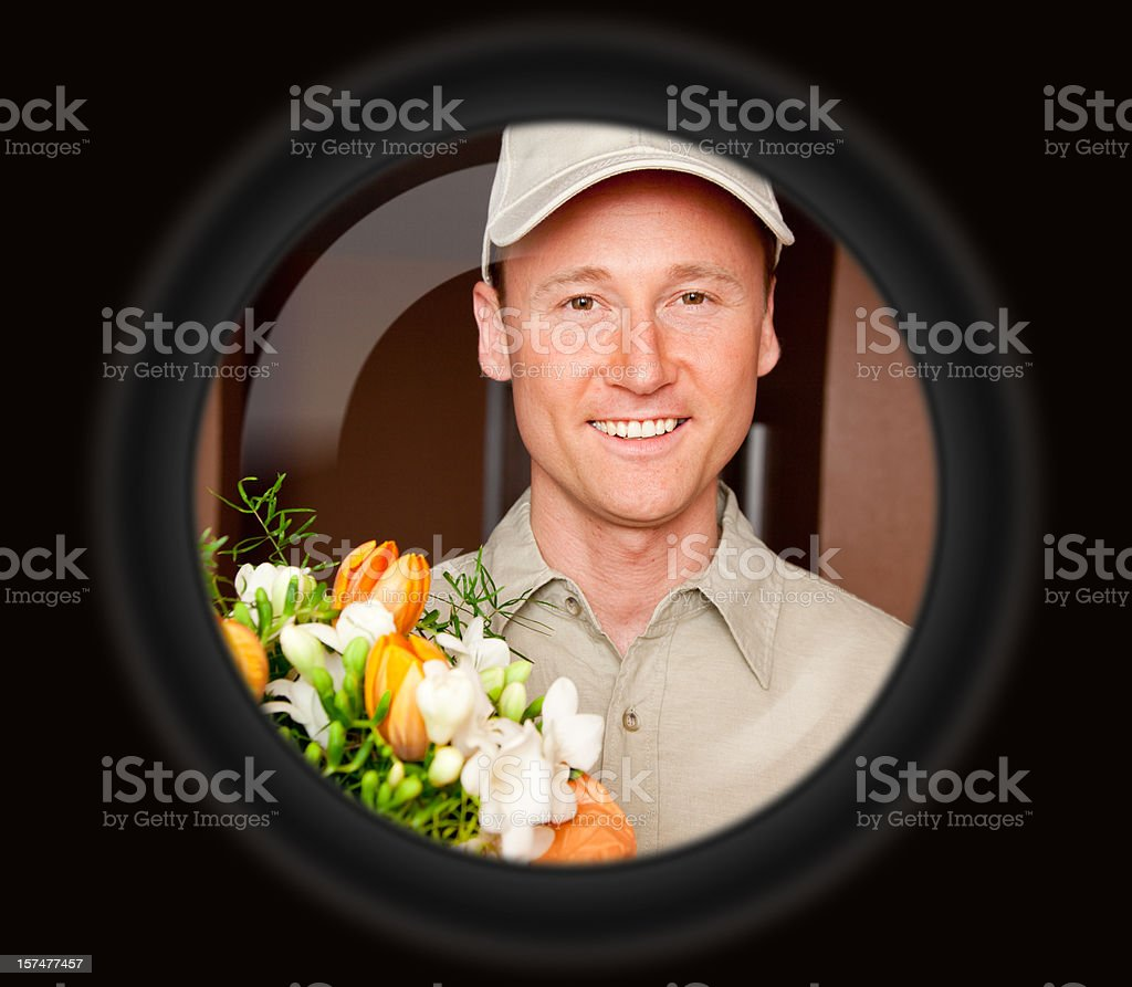 delivery boy with flowers seen through door viewer stock photo