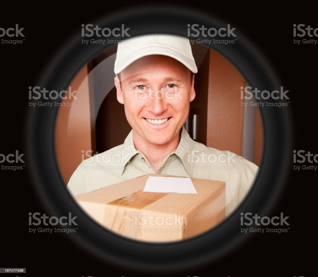delivery boy with packets seen through door viewer stock photo