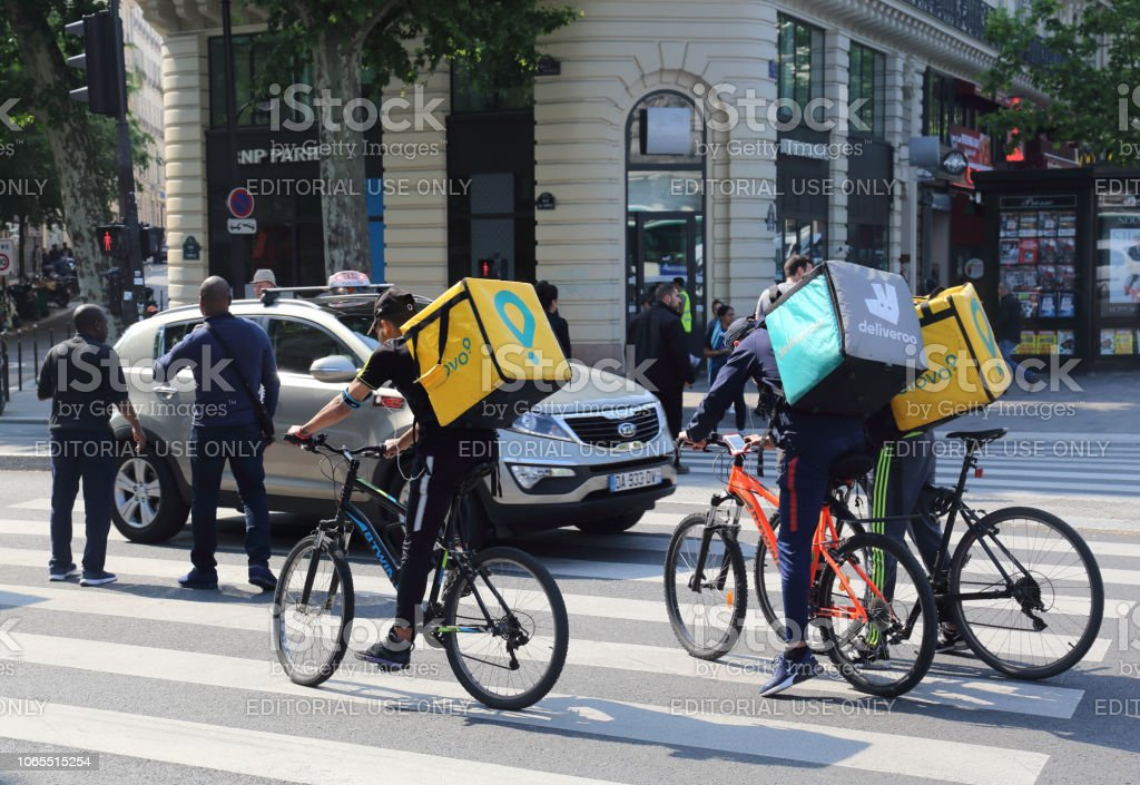 Delivery boys on bicycles in Paris, France stock photo