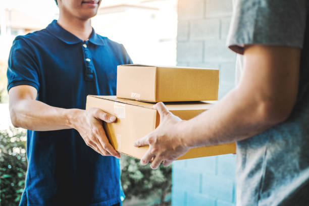 Delivery concept Asian Man hand accepting a delivery boxes from professional deliveryman at home stock photo