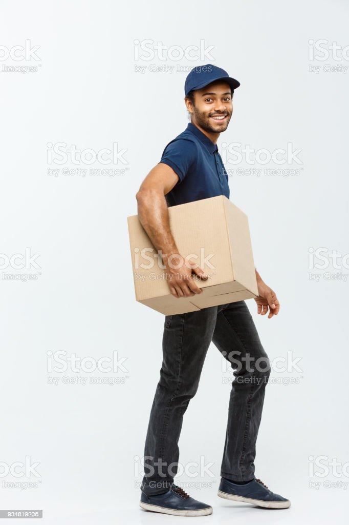 배달 개념-상자 패키지 고객에 게 보낼 걷는 파란 피복에서 행복 한 아프리카계 미국인 배달 남자의 초상화. 에 격리 된 회색 스튜디오 배경입니다. 공간에 복사 합니다. - 로열티 프리 남성 스톡 사진