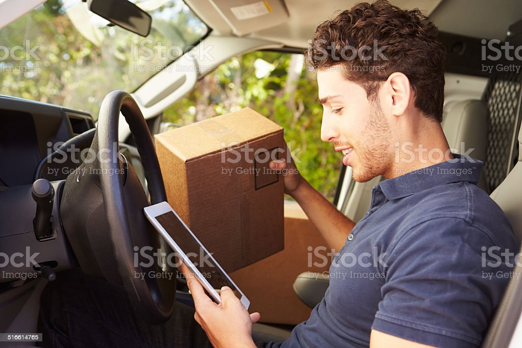 Delivery Driver Sitting In Van Using Digital Tablet stock photo