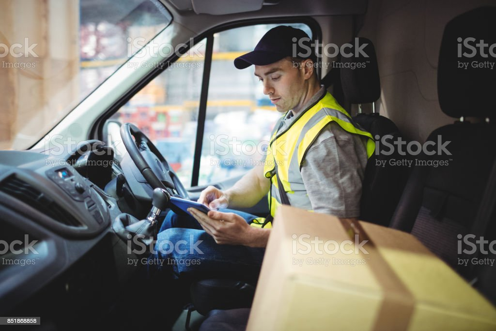 Delivery driver using tablet in van with parcels on seat stock photo