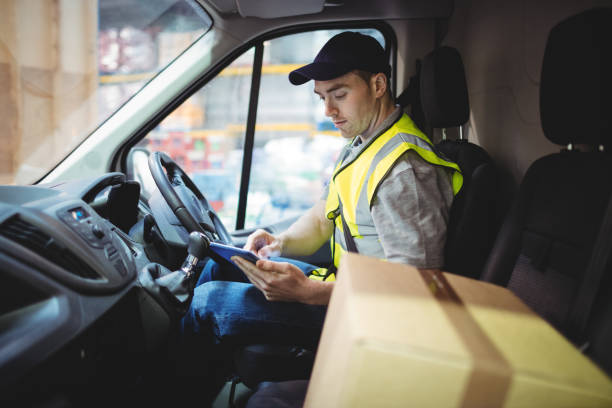 Delivery driver using tablet in van with parcels on seat Delivery driver using tablet in van with parcels on seat outside warehouse delivery man stock pictures, royalty-free photos & images