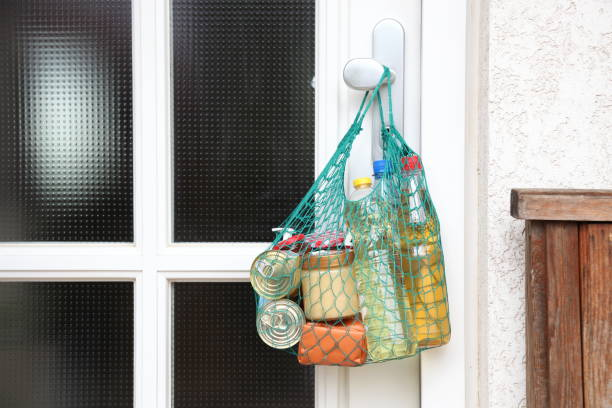 delivery during coronavirus infection Covid-19 quarantine. Shopping bag with Merchandise, goods, food hanging at the front door, neighborhood Assistance. helping of vulnerable people near you concept stock photo