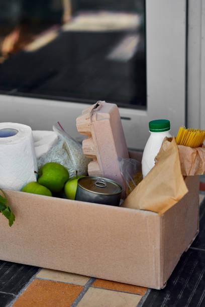 Lieferung während der Quarantäne. Box mit Waren, Waren und Lebensmitteln vor der Haustür – Foto