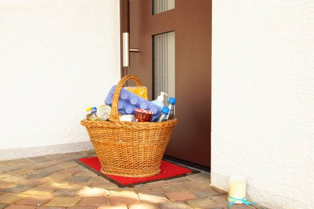 delivery during the quarantine. full willow wicker basket with Merchandise, goods and food in front of the door, neighborhood Assistance concept at quarantine time  of coronavirus infection Covid-19 stock photo