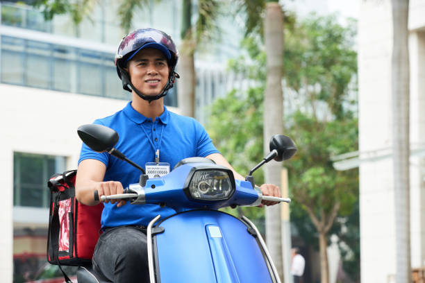 Delivery guy Vietnamese delivery man riding on scooter delivery man stock pictures, royalty-free photos & images