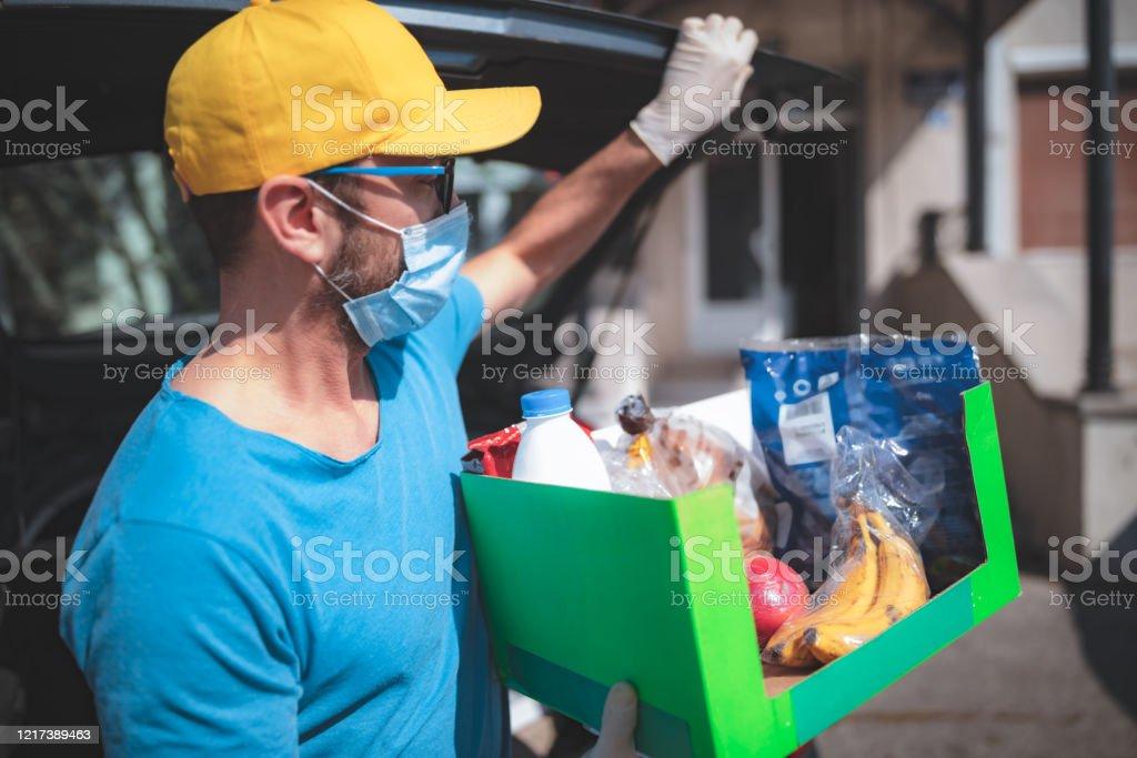 El repartidor con máscara protectora y guantes entregando alimentos durante el encierro y la pandemia. - Foto de stock de Adulto libre de derechos