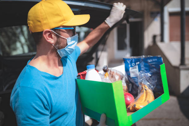 delivery guy with protective mask and gloves delivering groceries during lockdown and pandemic. - food delivery zdjęcia i obrazy z banku zdjęć