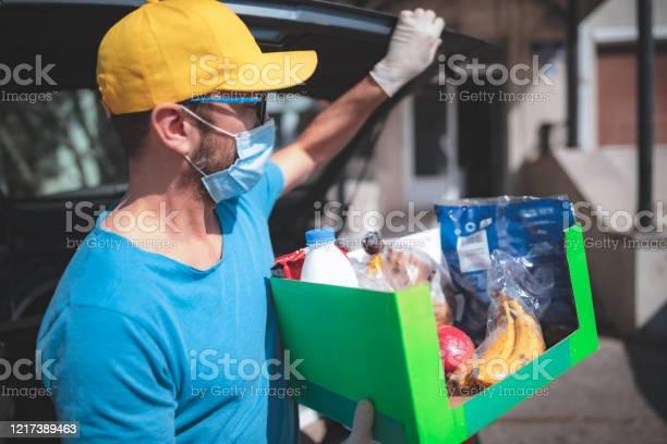 Delivery Guy With Protective Mask And Gloves Delivering Groceries During Lockdown And Pandemic - zdjęcia stockowe i więcej obrazów Artykuły spożywcze