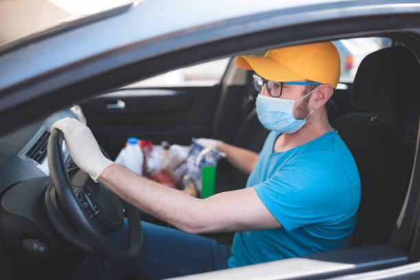 Liefermann mit Schutzmaske und Handschuhen Delovering Lebensmittel während Der Sperrung und Pandemie. – Foto