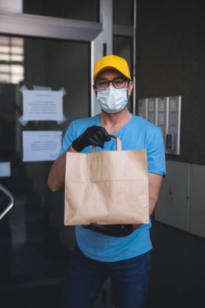 Liefermann mit Schutzmaske und Handschuhen Haltebox / Tasche mit Lebensmitteln vor einem Gebäude. – Foto