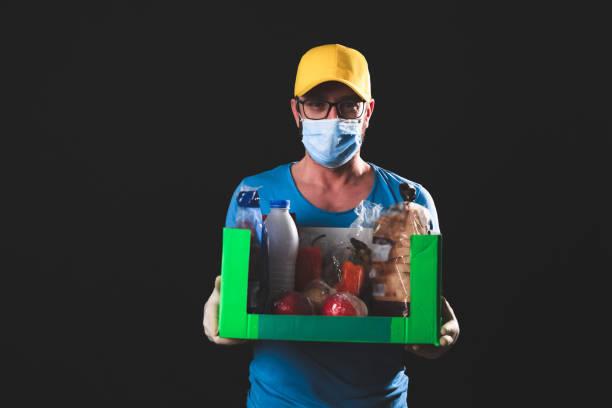 Liefermann mit Schutzmaske Haltebox mit Lebensmitteln während der Tage der Pandemie und Isolation Quarantäne. – Foto