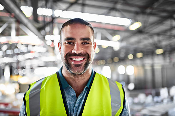 Delivery is my game Portrait of a warehouse worker standing in a large warehouse reflective clothing stock pictures, royalty-free photos & images