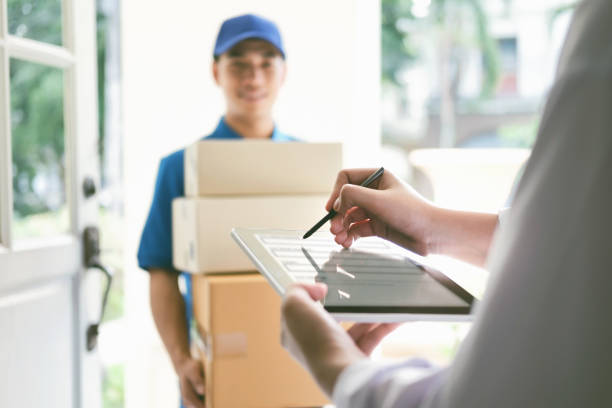 Delivery, mail, people and shipping concept. delivery, mail, people and shipping concept.Young woman sign in digital mobile phone after receiving parcel from courier at home. delivery man stock pictures, royalty-free photos & images