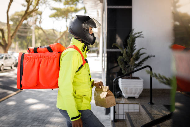 Delivery man arriving on destination side view - motoboy stock photo