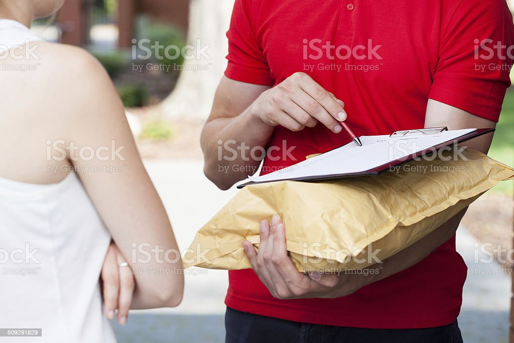 Delivery man asking for a signature stock photo