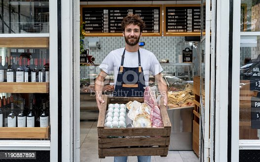 Delivery man at a deli holding a box with products for a customer smiling at camera very happy