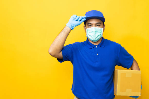 delivery man blue uniform wearing rubber gloves and mask holding parcel cardboard box on yellow background. - essential workers stock pictures, royalty-free photos & images