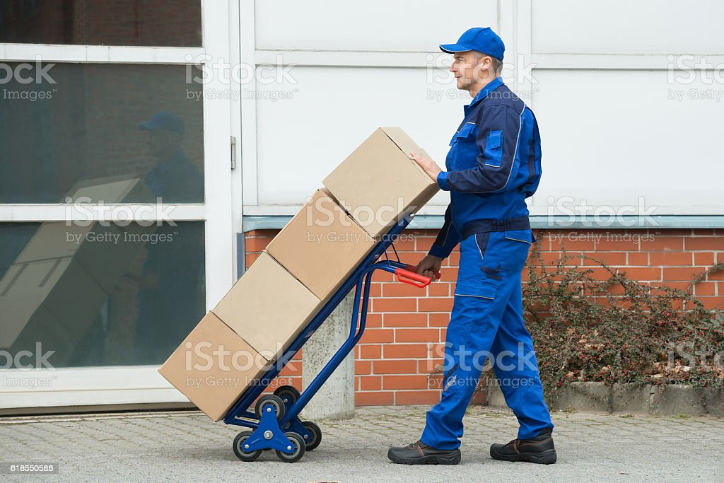Delivery Man Carrying Boxes On A Hand Truck stock photo
