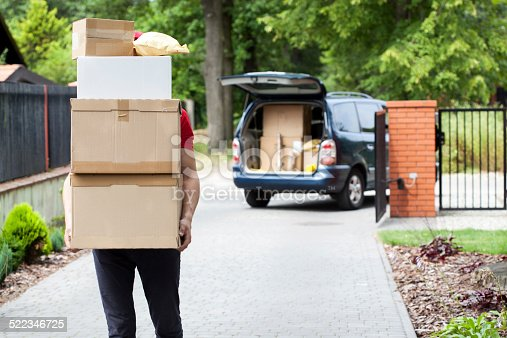 istock Delivery man carrying package stack 522346725