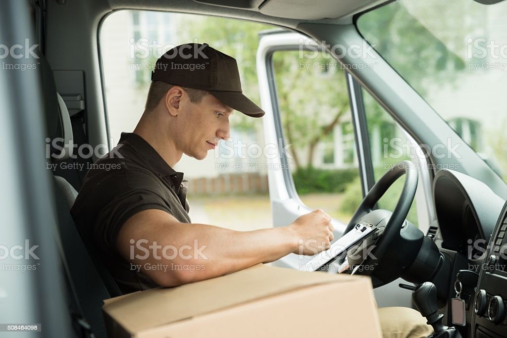 Delivery Man Checking List In Van stock photo