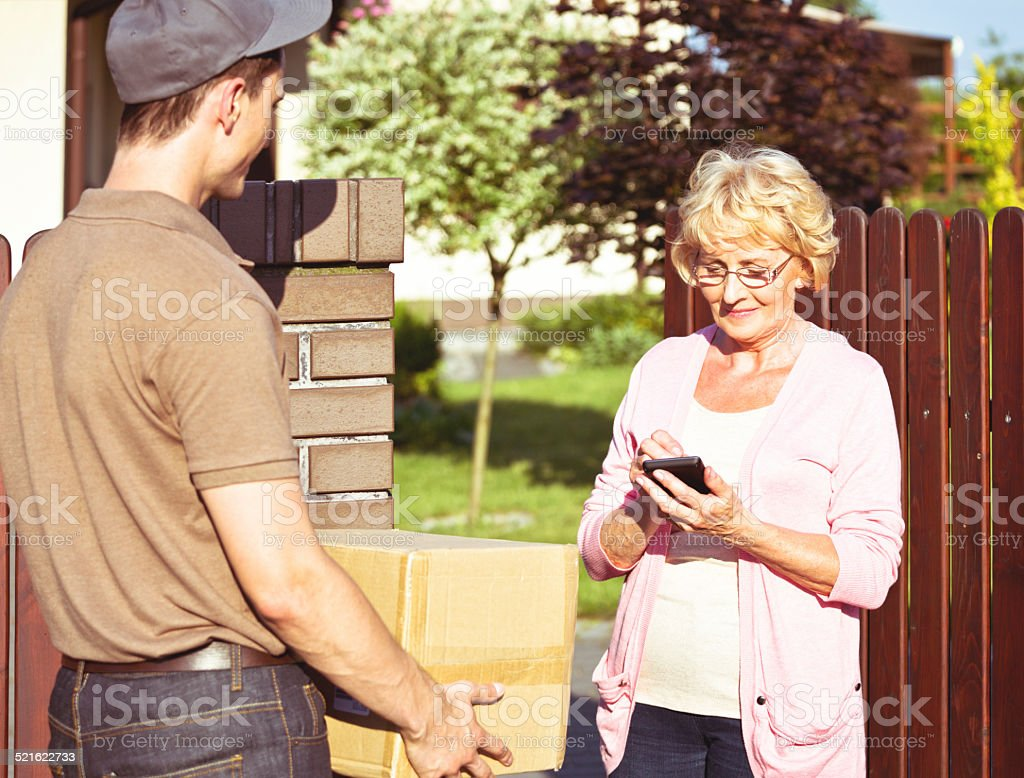 Delivery man delivering a parcel for senior woman Senior woman standing outdoor in front of her house, signing on palmtop while delivery man holding a parcel.  Active Seniors Stock Photo