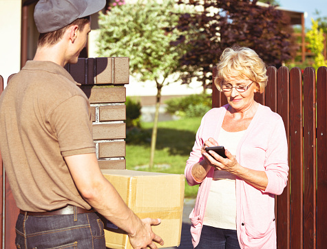 Delivery Man Delivering A Parcel For Senior Woman Stock Photo - Download Image Now