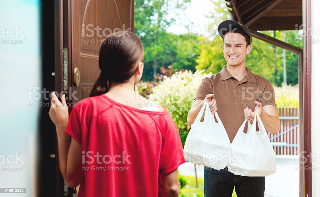 Delivery man delivering chinese take away food Young delivery man delivering chinese take away food for young woman, standing at the entrance door and holding two plactic bags in hands. Adult Stock Photo