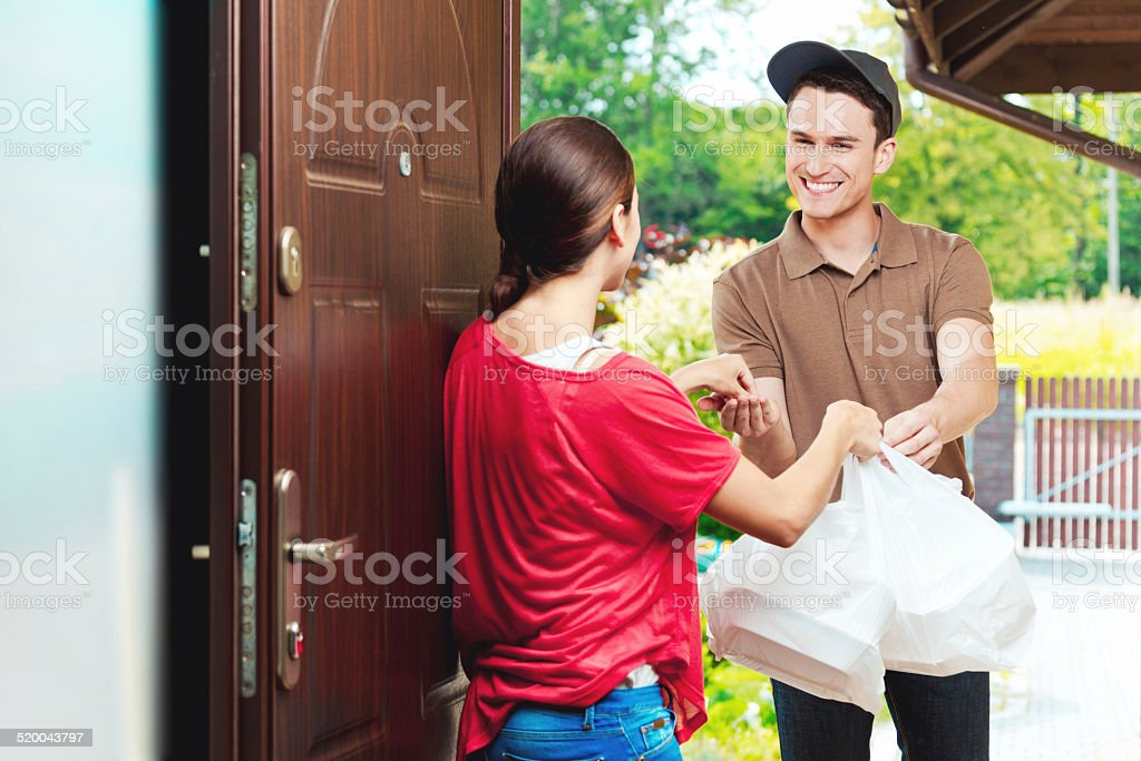 Delivery man delivering chinese take away food Young delivery man delivering chinese take away food for young woman, they standing at the entrance door. Adult Stock Photo