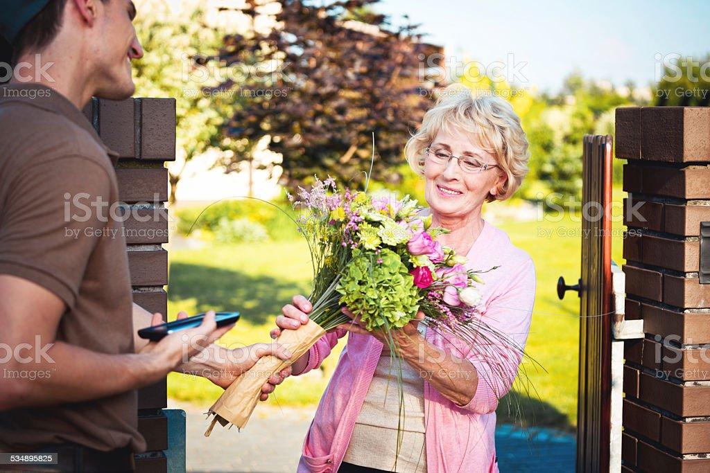 Lieferung Mann liefern Blumen für Ältere Frau – Foto