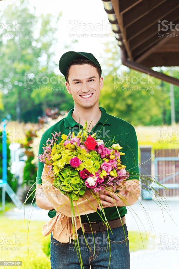 Delivery man delivering flowers Delivery man delivering a bouquet, standing in the entrance door and holding flowers, smiling at camera. Adult Stock Photo