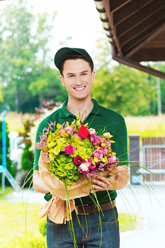 Delivery Man Delivering Flowers Stock Photo - Download Image Now