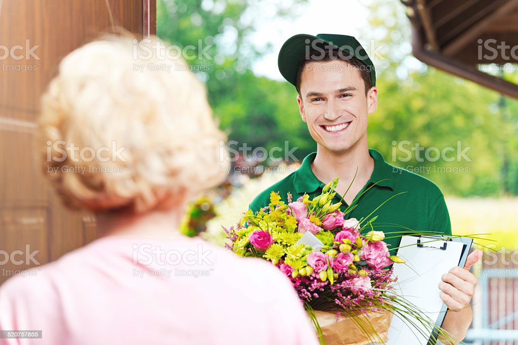 Delivery man delivering flowers Delivery man delivering a bouquet for mature woman, standing in the entrance door and holding flowers and clip board. 20-24 Years Stock Photo