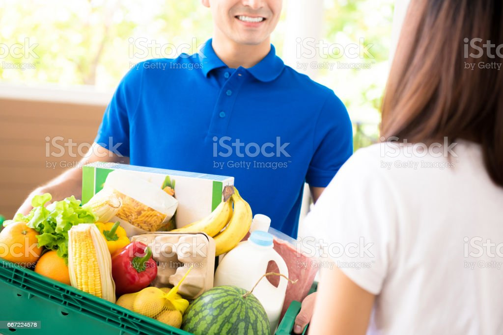 Delivery man delivering food to a woman at home stock photo